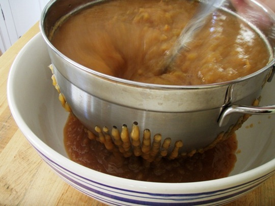 Strain applesauce through colander